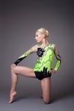 Donna di bellezza nel vestito del gymnast che propone sul grey Fotografia Stock Libera da Diritti