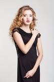 Donna di bellezza in un'acconciatura nera del fondo di bianco di vestito Fotografie Stock
