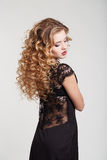 Donna di bellezza in un'acconciatura nera del fondo di bianco di vestito Fotografia Stock