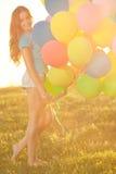 Donna di buon compleanno contro il cielo con degli gli aerostati colorati d'arcobaleno  Fotografia Stock Libera da Diritti