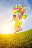 Donna di buon compleanno contro il cielo con delle le sedere colorate d'arcobaleno dell'aria Immagine Stock