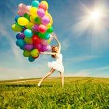 Donna di buon compleanno contro il cielo con delle le sedere colorate d'arcobaleno dell'aria Fotografia Stock