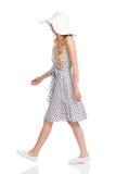 Donna di camminata in vestito, cappello di Sun e scarpe da tennis punteggiati bianco Fotografie Stock