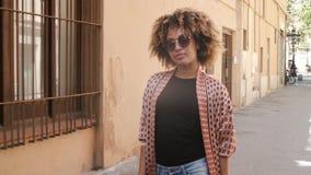 Donna di colore alla moda sicura che cammina sulla via archivi video