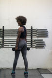 Donna di colore che fa i riccioli del bicipite fotografie stock libere da diritti