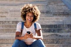 Donna di colore che si siede sui punti con lo Smart Phone e che ride all'aperto Fotografie Stock