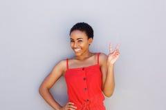 Donna di colore che sorride contro la parete grigia con il segno della mano di pace fotografia stock libera da diritti