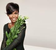 Donna di colore con fiori immagine stock