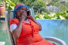 Donna di colore con l'espressione sorpresa sul suo fronte e sulla tenuta della sua mano alla sua bocca mentre parlando su un cell immagini stock libere da diritti