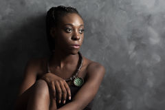 Donna di colore con la collana etnica che guarda alla destra; fotografia stock libera da diritti