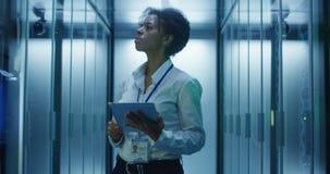 Donna di colore con la compressa che funziona nella stanza del server archivi video
