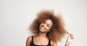 Donna di colore di Beuayt con i capelli enormi di afro divertendosi sorridere e contatto dei suoi capelli video d archivio