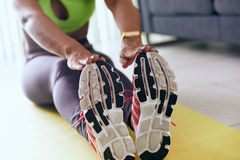 Donna di colore domestica di forma fisica che fa allenamento che allunga sul cuscinetto fotografie stock libere da diritti