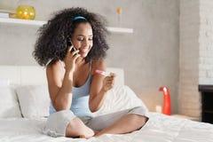 Donna di colore felice con il test di gravidanza Kit And Telephone fotografie stock