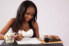 Donna di colore graziosa con il taccuino Fotografia Stock