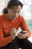 Donna di colore graziosa su PDA immagine stock