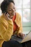 Donna di colore graziosa sul telefono e sul computer portatile delle cellule Immagini Stock