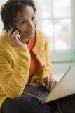 Donna di colore graziosa sul telefono e sul computer portatile delle cellule Fotografia Stock Libera da Diritti