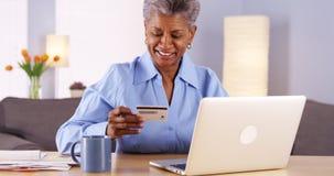 Donna di colore matura che paga felicemente le sue fatture Immagine Stock Libera da Diritti