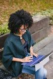 Donna di colore professionale che lavora con il computer portatile fuori in autunno immagine stock
