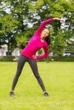 Donna di colore sorridente che allunga gamba all'aperto Fotografia Stock