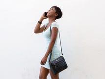 Donna di colore sorridente che cammina con il telefono cellulare Fotografie Stock Libere da Diritti