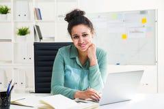 Donna di colore sorridente che per mezzo del computer portatile Immagini Stock