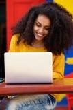 Donna di colore sorridente che per mezzo del computer portatile al caffè Fotografia Stock Libera da Diritti