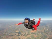 Donna di colore sorridente che salta dal paracadute fotografie stock libere da diritti