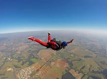 Donna di colore sorridente che salta dal paracadute immagine stock
