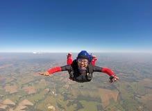 Donna di colore sorridente che salta dal paracadute fotografia stock