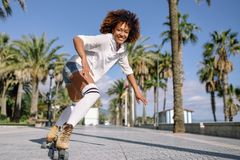 Donna di colore sui pattini di rullo che rollerblading nei wi della passeggiata della spiaggia immagine stock libera da diritti