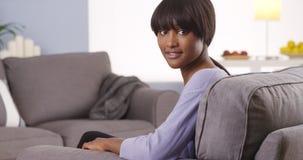 Donna di colore sveglia con i colpi che esaminano macchina fotografica Immagine Stock Libera da Diritti