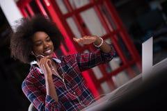 Donna di colore in ufficio moderno nel suo luogo di lavoro che speeking sul telefono Fotografia Stock Libera da Diritti