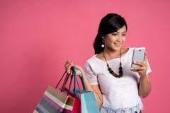 Donna di compera che per mezzo dei sacchetti della spesa della tenuta e dello smartphone fotografia stock