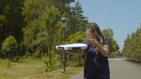 Donna di consegna della pizza sulle lame del rullo in parco archivi video