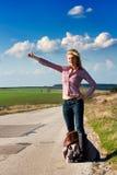 Donna di corsa che fa auto-stop Fotografie Stock
