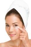 Donna di cura di pelle che mette la crema di fronte Fotografia Stock Libera da Diritti