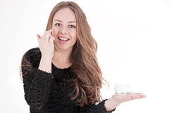 Donna di cura di pelle che mette la crema di fronte Fotografia Stock