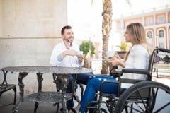 Donna di datazione dell'uomo in una sedia a rotelle Fotografia Stock