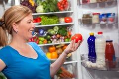 Donna di dieta e di nutrizione che sta frigorifero vicino con i frutti Fotografia Stock