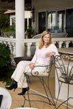 donna di distensione delle feci del patio maturo della barra fotografie stock