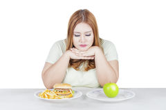 Donna di dubbio che sceglie alimento immagini stock libere da diritti