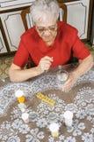 Donna di Ederly che cattura le pillole Fotografia Stock Libera da Diritti