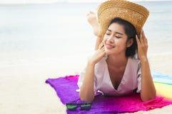 Donna di estate che si rilassa nel cappello della spiaggia dei pantaloni a vita bassa e nei sunglass variopinti Immagine Stock