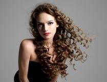 Donna di fascino con capelli lunghi ricci Fotografie Stock