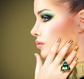 Donna di fascino con i bei chiodi dorati e l'anello verde smeraldo Immagine Stock