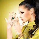 Donna di fascino con i bei chiodi dorati e l'anello verde smeraldo Fotografia Stock