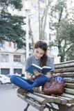 Donna di felicità che si siede sul libro di lettura e del banco, all'aperto Fotografie Stock