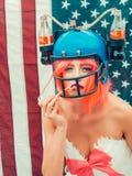 Donna di festa dell'indipendenza con il casco della bevanda e della bandiera Immagine Stock